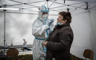 epa08788104 An Austrian Military medic collects a swab sample from a person at a coronavirus disease testing site during a nationwide testing in Bratislava, Slovakia, 31 October 2020. A total of 50 Austrian military medics help Slovakia with the mass testing.  EPA/JAKUB GAVLAK