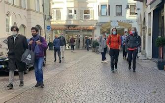 Persone passeggiano per Bolzano, 02 novembre 2020. Visto l'alto numero dei contagi da conronavirus, l'Alto Adige ha deciso un nuovo lockdown per tre settimane. Dalle ore 20 alle ore 5 del mattino vi sarà un divieto di circolazione, semprechè non vi siano necessità non rinviabili. Verranno chiusi bar, ristoranti, pasticcerie e negozi. ùANSA/G.News