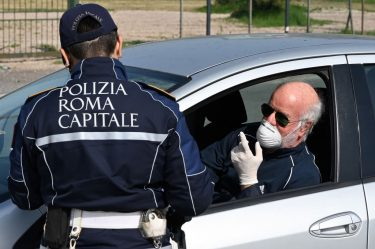 A member of the Rome Local Police checks the documents and the self-declaration of a motorist, wearing a facemask for protective reasons, on the Via Pontina, in Rome, on March 21, 2020, during the country's lockdown aimed at stopping the spread of the COVID-19, the novel coronavirus. - Italy reported a record 627 new coronavirus deaths on March 20, 2020 and saw its world-topping toll surpass 4,000, despite government efforts to stem the pandemic's spread. (Photo by Alberto PIZZOLI / AFP) (Photo by ALBERTO PIZZOLI/AFP via Getty Images)