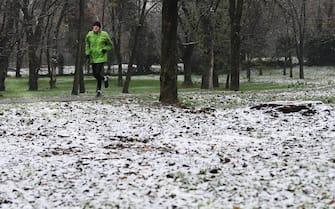 Una persona corre in un parco di San Donato Milanese ricorperto di un leggero strato di neve, 2 dicembre 2020. ANSA/DANIEL DAL ZENNARO