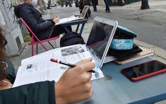 Immagine di Dad in strada a Torino, con un banco e un tablet
