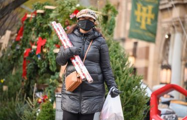 NEW YORK, NEW YORK - DECEMBER 11: A person carries gift wraps on the Upper West Side on December 11, 2020 in New York City.  Many holiday events have been canceled or adjusted with additional safety measures due to the ongoing coronavirus (COVID-19) pandemic. (Photo by Noam Galai/Getty Images)
