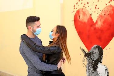 Emergenza Corona Virus.  La vita ai tempi del Corona Virus.  L amore ai tempi del corona virus. Una coppia di fidanzati con mascherina anti contagio  si abbraccia davanti ad un murales .  15 Marzo 2020. Padova  ANSA/NICOLA FOSSELLA