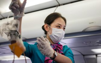 epa08185837 A flight attendant of Cambodian Lanmei Airlines demonstrates safety procedures in the airplane while wearing a face mask during a flight from Sihanoukville, Cambodia, via Phnom Penh, Cambodia to Guangzhou, Guangdong Province, China, 01 February 2020. Guangzhou Airport usually busy during the end of Spring Festival when Chinese travelers return to their homes, appears deserted after many countries and international airlines are suspending or limiting flights routes to China, including American Airlines, British Airways, and Lufthansa, because of outbreak of Coronavirus in Wuhan City, Hubei Province. Rare passengers who were able to board airplanes to China, are required to fill health declaration forms explaining if they were in Hubei Province in last 14 days and their body temperature is monitored several times on the terminal.  EPA/Alex Plavevski