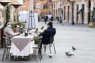 Clienti seduti ai tavoli fuori da un bar fanno colazione a Roma