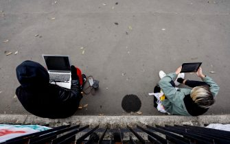 Due ragazzi ripresi dall'alto seduti e con in grembo dei pc