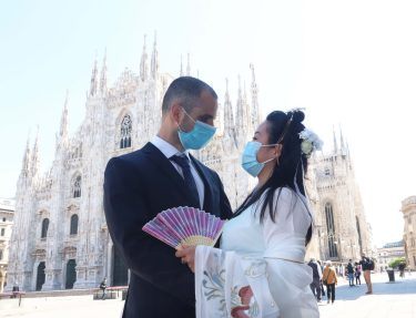 MILAN, ITALY - MAY 7: An Italian citizen and a young Chinese woman wear surgical masks while they hug at finish of  marriage ceremony at Milan Cathedral  during the end of the lockdown amid of the coronavirus lockdown on May 6, 2020 in Milani, Italy on May 7, 2020 in Milan, Italy//EYEPIX_1.3302/2005081135/Credit:Clemente Marmorino/SIPA/2005081135
