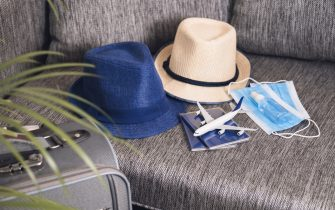 Prepairing for travel after the end of quarantine Passports, hats, face masks and hand sanitizer Flight rules during coronavirus pandemic.