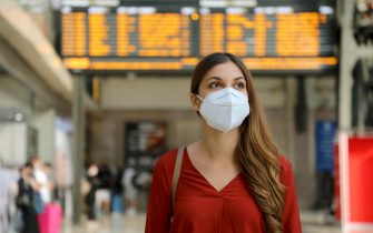 Traveler woman wearing KN95 FFP2 face mask at train station to protect from virus and smog. Young caucasian woman with timetables information of departures arrivals on behind.
