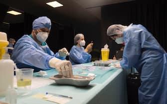 Operatore sanitario maneggia una siringa col vaccino anti-Covid