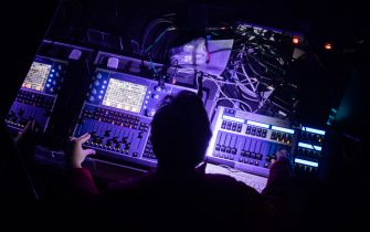 "27 March 2021, Berlin: A person operates a mixing console at a test concert entitled ""Operation Heartbeat"" in the ""Säälchen"" on the Holzmarkt. All event participants took a Corona quick test in advance. The project aims to test the logistical feasibility of events in conjunction with Sars-CoV-2 antigen testing in order to develop feasible scenarios for the reopening of the culture. Photo: Christoph Soeder/dpa"