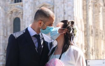 MILAN, ITALY - MAY 7: An Italian citizen and a young Chinese woman wear surgical masks while they kiss at finish of  marriage ceremony at Milan Cathedral  during the end of the lockdown amid of the coronavirus lockdown on May 6, 2020 in Milani, Italy on May 7, 2020 in Milan, Italy//EYEPIX_1.3299/2005081134/Credit:Clemente Marmorino/SIPA/2005081135