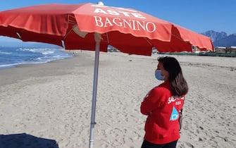 Una bagnina con la mascherina un una spiaggia italiana