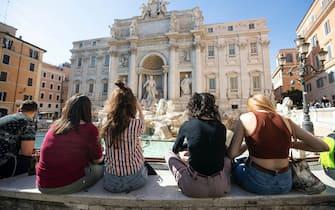 Roma in zona gialla, ragazzi seduti alla Fontana di Trevi