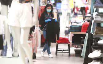 Una commessa con la mascherina sistema i vestiti nel suo negozio