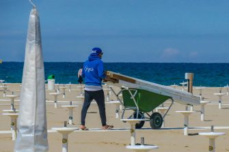 """Beach staff prepares poles for the installation of parasols at """"Bagno 62"""" on the Adriatic  coast on the first day of the bathing season in Rimini, Italy, 15 May 2021. Italy is significantly easing its COVID-19-linked restrictions. ANSA/PASQUALE BOVE"""