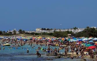 Una veduta della spiaggia di Pescoluse (Lecce), nel Salento, piena di bagnanti e ombrelloni