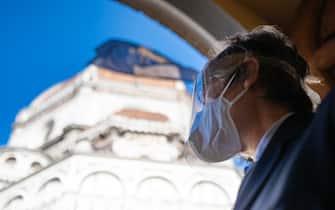 Un monumento di Firenze con un turista con la mascherina