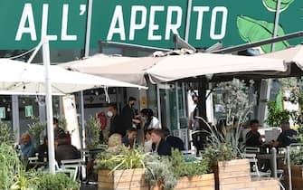 Persone pranzano sedute ai tavoli di un bar-ristorante, Milano, 17 maggio 2021. Gli esercizi commerciali in mercati e centri commerciali, gallerie e parchi commerciali nelle giornate festive e prefestive riapriranno dal 22 maggio, nel primo weekend successivo al decreto legge Covid. ANSA/DANIEL DAL ZENNARO