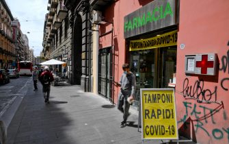"""Cartello """"tamponi rapidi Covid-19"""" all'ingresso di una farmacia"""