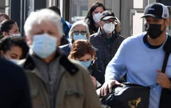 Persone con i volti coperti da una mascherine camminano in una via del centro, Milano, 24 febbraio 2021.ANSA/DANIEL DAL ZENNARO
