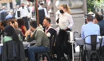 Una cameriera, con il volto coperto da una mascehrina sanitaria, serve un cliente in un ristorante nel centro di Milano, 28 maggio 2021.Il 23% degli italiani ha intenzione di andare al ristorante o al bar nei prossimi mesi molto più spesso di come ha fatto nel 2019. E' quanto emerge da un sondaggio Ipsos, secondo il quale, inoltre, in una scala da 1 a 10, la mancanza di pranzi o cene fuori casa, soprattutto per passare tempo con la famiglia e gli amici raggiunge quasi il punteggio massimo (8,4) e per quanto riguarda le scelte del menù, in futuro il 61% presterà molta più attenzione alla qualità che alla spesa e il 73% alla salute, contro un 23% che continuerà a puntare al 'gusto senza compromessi'. ANSA/DANIEL DAL ZENNARO