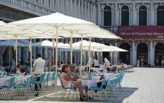 Turisti siedono ai tavoli sotto gli ombrelloni nel plateatico del caffè Aurora, in piazza San Marco, stamane 26 giugno 2020. ANSA/ANDREA MEROLA