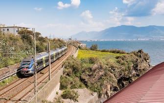 Un treno mentre viaggia lungo la costa italiana