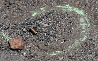 Un bossolo nei pressi del campo dove un uomo ha sparato e ucciso due bambini e un signore anziano ad Ardea, Roma, 13 giugno 2021. ANSA/CLAUDIO PERI
