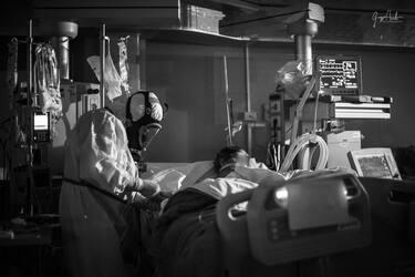 """""""Nell'Aprile 2020, causa emergenza covid, ho iniziato il mio incarico nell'Unità Operativa di Anestesia e rianimazione presso il P.O. """"Giovanni Paolo II"""" di Sciacca.Tutto è iniziato con il progetto di umanizzazione deciso dalla Direzione dell'ASP di Agrigento. Ho collaborato attivamente, insieme al Primario Francesco Petrusa, al coordinatore Marco Li Gioi e a tutto il personale sanitario nella personalizzazione delle tute anti-covid affiggendo su di esse le foto dei volti  e i nomi di chi le indossava. A tal fine, i pazienti ricoverati, che prima di allora ci vedevano completamente imbardati, hanno potuto quantomeno riconoscere chi fosse a prendersi cura di loro. Tutto ciò era teso a ripristinare quel contatto umano che purtroppo in quei mesi di pandemia è venuto tristemente a mancare.  Il successo del progetto mi ha coinvolto emotivamente così tanto da continuare a voler scattare altre foto che raccontassero i sacrifici e la determinazione di noi professionisti sanitari alle prese con l'emergenza. Raccontare le nostre storie a chi, quella tragedia non l'ha mai vissuta.  Da settembre 2020 fino alla chiusura della nostra terapia intensiva covid, avvenuta a fine maggio 2021. Ho archiviato circa 200 scatti inerenti l'emergenza sanitaria.  Durante la seconda ondata ben presto ci siamo ritrovati con tutti i posti letto occupati. Il carico di lavoro era estenuante e a tratti umanamente impossibile da sopportare. Dentro le tute si sudava parecchio e spesso le visiere si appannavano. Non potevamo bere o andare in bagno.  Gli allarmi dei monitor suonavano in continuazione e noi ci destreggiavamo tra dozzine di cavi, deflussori e circuiti per la ventilazione polmonare.  Abbiamo continuato a lottare anche quando, idolatrati come eroi, ben presto siamo divenuti gli untori e assassini. Nonostante tutto abbiamo continuato con professionalità e senso del dovere ad assistere quelle persone anche quando siamo stati aggrediti, derisi e insultati da chi a quel virus così subdolo e let"""