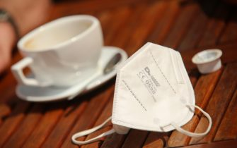 01 June 2021, Saxony-Anhalt, Quedlinburg: An FFP2 mask lies next to a cup of coffee on a table. In Saxony-Anhalt, outdoor and indoor catering has reopened under restrictions. Photo: Matthias Bein/dpa-Zentralbild/dpa (Photo by Matthias Bein/picture alliance via Getty Images)