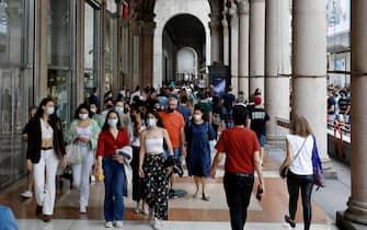 Gente per strada a Milano con la mascherina