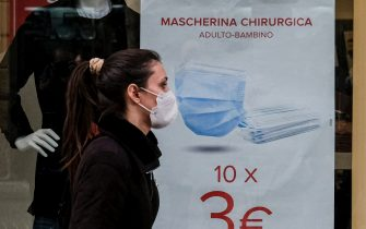 VOMERO DISTRICT, NAPLES, CAMPANIA, ITALY - 2021/01/11: A woman wearing protective mask passes in front of a shop window on the first day of sales where are an advertising poster promotes the offer of 10 surgical masks for 3 euros. (Photo by Antonio Balasco/KONTROLAB/LightRocket via Getty Images)