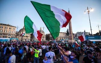 Tifosi azzurri sventolano bandiere dell'Italia in piazza del Popolo, a Roma, durante una partita di Euro 2020