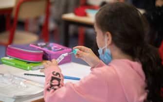 Una bambina a scuola con la mascherina