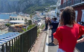 Alcune persone osservano dalla strada il bus precipitato a Capri