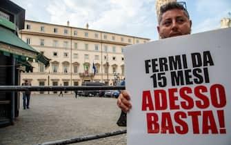 Gestore mostra un cartello di protesta alla manifestazione per la riapertura delle discoteche in Piazza San Silvestro, a Roma, l'8 luglio 2021