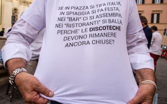 Una t-shirt mostrata alla manifestazione dei gestori delle discoteche in Piazza San Silvestro, a Roma, l'8 luglio 2021
