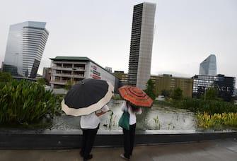 Persone camminano sotto la pioggiaa causa del maltempo a Milano, 26 luglio 2021. ANSA/DANIEL DAL ZENNARO