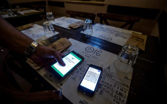 A visitor's Covid-19 Green Pass is checked at the entrance to a restaurant in Rome, Italy, 09 August 2021. Effective from 06 August, the so-called Green Pass is advocated by the government as the alternative to lockdowns in the light of the spreading Delta variant of the Sars-Cov-2 pandemic coronavirus. People who do not hold the certificate that identifies them as either immunised, recovered or tested for Covid-19 may be excluded from indoor venues and for access to amusement parks it is necessary to be up to date with anti-covid-19 vaccinations, or have a negative swab in the last 48 hours. ANSA/ANGELO CARCONI