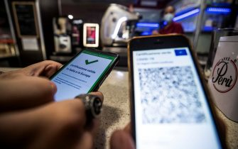 A visitor's Covid-19 Green Pass is checked at the entrance to a bar in Rome, Italy, 09 August 2021. Effective from 06 August, the so-called Green Pass is advocated by the government as the alternative to lockdowns in the light of the spreading Delta variant of the Sars-Cov-2 pandemic coronavirus. People who do not hold the certificate that identifies them as either immunised, recovered or tested for Covid-19 may be excluded from indoor venues and for access to amusement parks it is necessary to be up to date with anti-covid-19 vaccinations, or have a negative swab in the last 48 hours. ANSA/ANGELO CARCONI