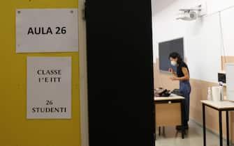 Insegnante con mascherina anti-Covid in classe durante una lezione