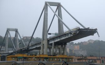 """A picture taken on August 14, 2018 in Genoa shows a view of the Ponte Morandi motorway bridge, after one of its section collapsed injuring several people. - Rescuers scouring through the wreckage after part of a viaduct of the A10 freeway collapsed said there were """"tens of victims"""", while images from the scene showed an entire carriageway plunged on to railway lines below. (Photo by ANDREA LEONI / AFP)        (Photo credit should read ANDREA LEONI/AFP via Getty Images)"""