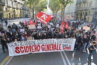 Un centinaio di studenti vicini ai centri sociali si sono dati appuntamento questa mattina in piazza Albarello, a Torino, per raggiungere in corteo la stazione di Porta Nuova nell'ambito della mobilitazione generale per lo sciopero dei trasporti, 11 Ottobre 2021. ANSA/ALESSANDRO DI MARCO