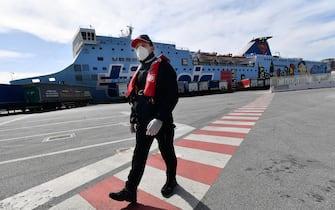 Un pilota del porto di Genova  si prepara per uscire con la pilotina verso una nave cargo da portare dentro il porto. Da ieri sono attive nuove regole per limitare al massimo i contatti tra i lavoratori portuali ed equipaggi. Genova, 17 Marzo 2020. ANSA/LUCA ZENNARO