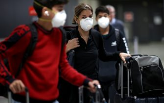 DULLES, VIRGINIA - MARCH 13: Passengers wearing masks arrive at Dulles International Airport March 13, 2020 in Dulles, Virginia. U.S. President Donald Trump announced restrictions on travel from Europe two days ago due to an outbreak of coronavirus (COVID-19). Today is the last day of unrestricted travel from Europe into the United States.  (Photo by Win McNamee/Getty Images)