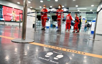 A marking on the ground (Bottom) indicates arriving passengers where to stand to undergo body temperature scanning, supervised by Red Cross volunteers (Rear) on May 5, 2020 at Rome's Fiumicino airport during the country's lockdown aimed at curbing the spread of the COVID-19 infection, caused by the novel coronavirus. (Photo by ANDREAS SOLARO / AFP) (Photo by ANDREAS SOLARO/AFP via Getty Images)