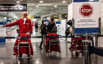 An airport staff directs passengers exiting an airplane that landed at Rome's Fiumicino airport from Paris on March 7, 2020 as part of body temperature screening procedures to prevent the spread of the new coronavirus. - Italy prepared on March 7, 2020 to quarantine more than 10 million people around the financial capital Milan and the tourist mecca Venice for nearly a month to halt the spread of the new coronavirus. A draft government decree published by Italy's Corriere Della Sera newspaper and other media said movement into and out of the regions would be severely restricted until April 3. (Photo by Laurent EMMANUEL / AFP) (Photo by LAURENT EMMANUEL/AFP via Getty Images)