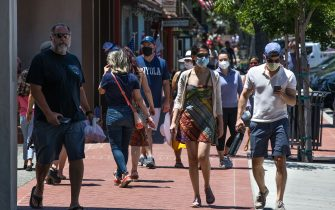 SOLVANG, CA - MAY 24:  Visitors to this Central Coast destination, some wearing face masks, are gradually arriving in large numbers to enjoy the Memorial Day Weekend and unofficial start to summer on May 24, 2020, in Solvang, California. Because of its close proximity to Southern California and Los Angeles population centers, this Danish-themed tourist attraction in Santa Barbara County has become a popular weekend travel getaway destination for millions of tourists each year. The town's hotels, restaurants (except for carry-out), wineries, and boutique shops had been closed for the past two months due to Covid-19.  (Photo by George Rose/Getty Images)