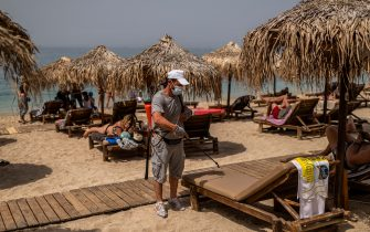 A man wearing a face mask disinfects a sunbed during the official reopening of beaches to the public in Athens on May 16, 2020. - Greece said on May 14, 2020 it will open 515 beaches from May 16 as a balmy weekend approaches, with applying strict social distancing measures to fight the spread of the COVID-19 pandemic, caused by the novel coronavirus. (Photo by Angelos Tzortzinis / AFP) (Photo by ANGELOS TZORTZINIS/AFP via Getty Images)